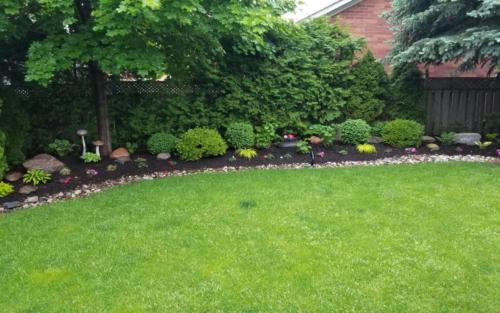 backyard garden with river stone edge