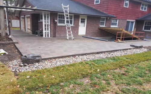 backyard paver patio with river stone