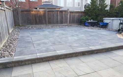 backyard paver patio with river stone border
